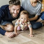 Dad, mom, and baby having fun on hardwood floors