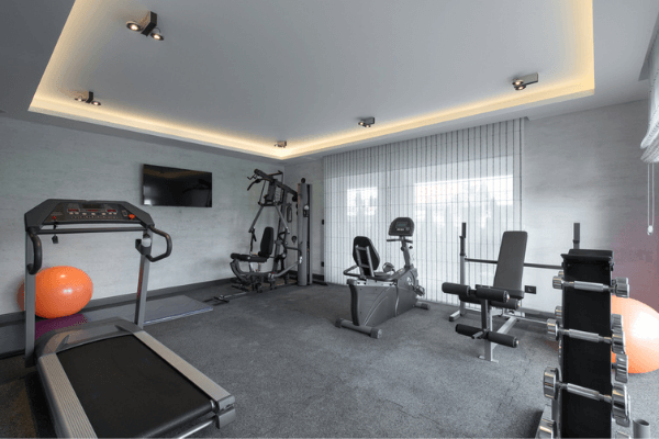 Dark grey coloured interlocking rubber tile flooring in a home gym with a treadmill, stationary bike, and other large equipment