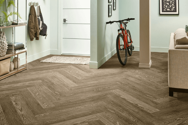 Luxury plank vinyl flooring at an entrance way in a herringbone pattern with a white door and a bike leaning on the wall.