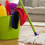 Green pail with floor cleaning supplies and a microfibre mop leaning against it   How To Clean Luxury Vinyl Floors?